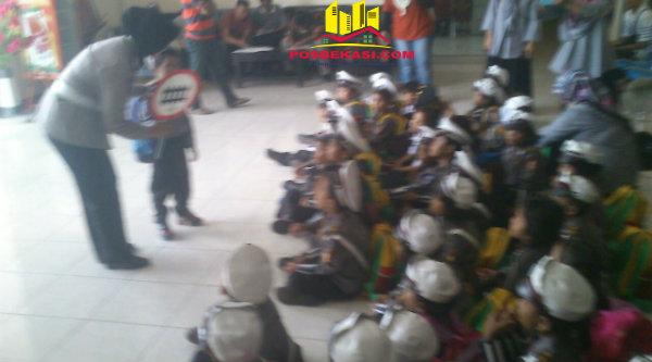 Seorang Polwan Polsek Medan Satria memperkenalkan rambu-rambu lalu lintas kepada murid TK Al -Washliyah. [EZI]