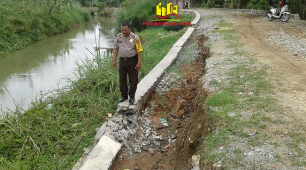 Binmaspol Muara Gembong, Aiptu Triyadi, saat mengecek kerusakan pondasi jalan.[YAN]