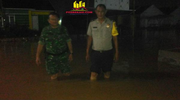 Bimaspol Aiptu Gigih PK di tengah banjir Perumahan Mustika Gandaria.[RIK]