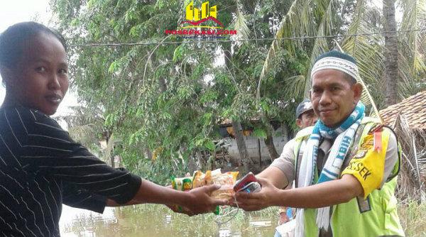 Kapolsek Muara Gembong AKP Sigit Sudarmono ketika menyalurkan bantuan pada korban di Desa Jaya Sakti.[SOF]