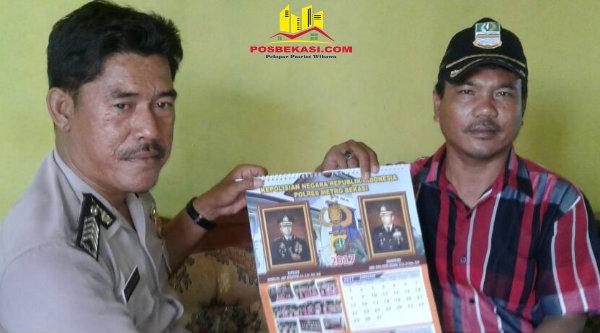 Binmaspol Muara Gembong Bripka Wahyudin memberikan kalender Polri pada tokoh masyarakat Desa Pantai Bahagia.[RIS]