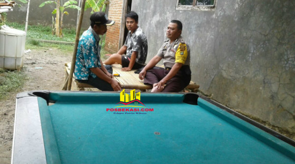 Binmaspol Desa Pantai Bakti, Aiptu Triyadi, mengimbau warga untuk tidak berjudi saat sambang kampung di Kampung Bendungan RT03/05, Rabu 8 Februari 2017.[MIN]