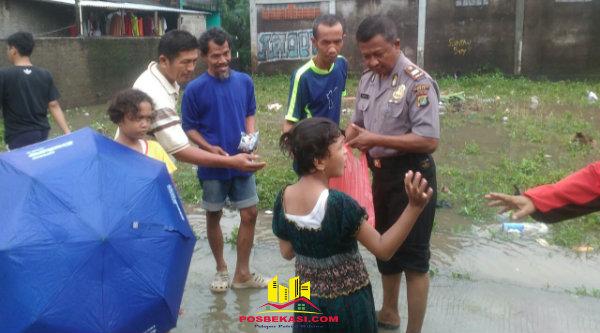 Kanit Binmas Polsek Tamsel Iptu Tarmuji membagikan nasi bungkus para korban banjir, Senin 20 Februari 2017.[RIS]