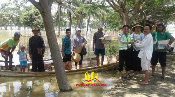 Warga Kampung Pangarengan menerima sembako dari Binmaspol Desa Jaya Sakti Bripka Saefulloh yang menyalurkan bantuan Polrestro Bekasi, Jumat 24 Februari 2017.[RIS]