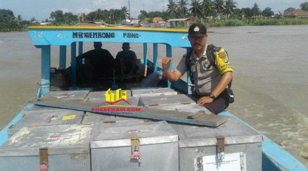 Binmaspol Pantai Bahagia Bripka Wahyudin mengawal perahu motor yang mengangkut logistik Pilkada ke Desa Pantai Bahagia.[HSB]