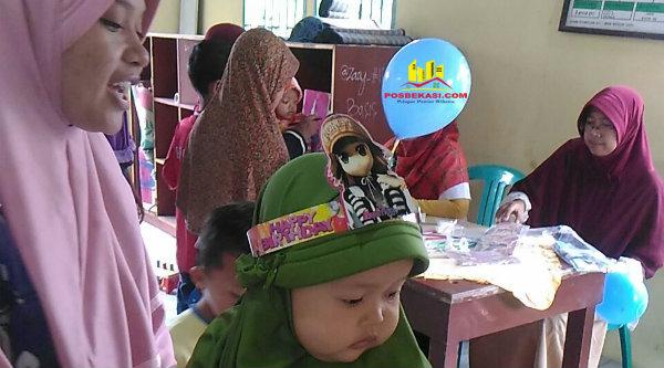 Seorang ibu membawa balitanya untuk mendapatkan vitamin A di Posyandu Kartini XIII.[IMA]