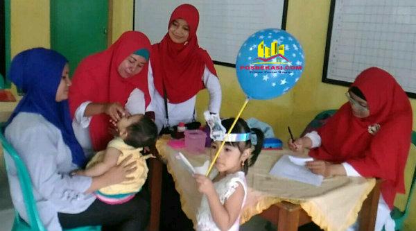 Kader Posyandu Kartini XIII tengah memberi vitamin A pada balita yang di pangku ibunya dan terlihat seorang balita memegang balon.[IMA]