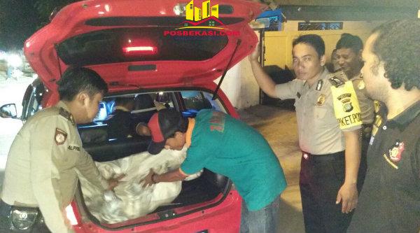 Anggota Polsek Muara Gembong yang menggelar Operasi Harkamtibmas malam hari memeriksa barang bawaan pengendara yang disimpan dalam bagasi mobil.[YAN]
