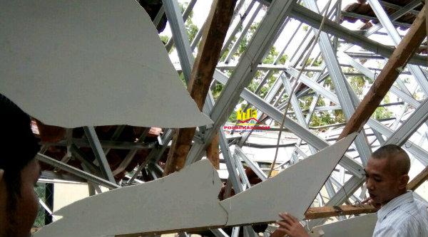 Seorang pelajar SMA Negeri 1 Muara Gembong di Puskesmas Muara Gembong berupaya menyelamatkan tas dan buku sekolahnya dari puing-puing konstruksi atap gedung sekolah yang ambruk, Selasa 28 Februari 2017.[HSB]