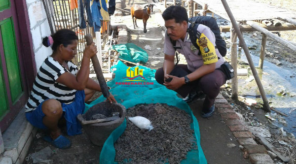 Binmaspol Desa Pantai Bahagia Bripka Wahyudin tengah bersama seorang ibu membuat trasi jambret untuk bertahan hidup ditengah banjir karena saat ini suaminya tidak dapat melaut.[OJI]
