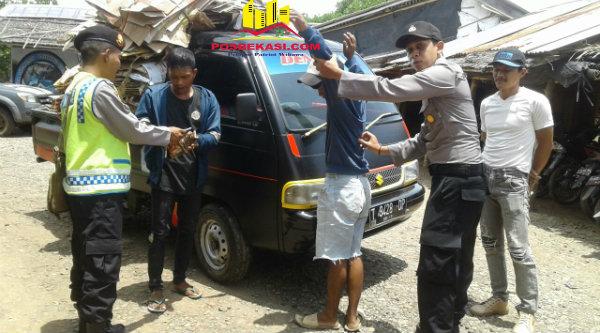 Operasi Siang: Kanit Patroli Aipda M Muji dan anggota Polsek Muara Gembong melakukan pemeriksaan dan penggeledahan pada kenderaan dan orang yang melintas di daerah operasi, Senin 6 Pebuari 2017.[YAN]