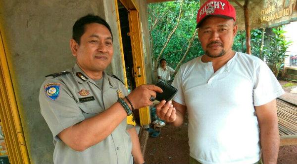Aiptu Yulianto mengantarkan dompet warga Cisaat yang tercecer di Jalan Raya Desa Cibening, Rabu 1 Maret 2017.[MIN]