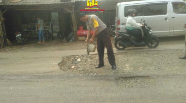 Aiptu Gigih PK mengurug Jalan Raya MT Haryono yang berlubang di Kampung Burangkeng.[MIN]