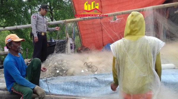Brigadir Alpon memeriksa jaring yang digunakan nelayan untuk menangkap ikan di laut Muara Gembong.[SUB]