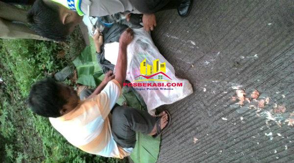 Anggota Polsek Setu dibantu seorang warga mengarungi kepala korban yang pecah, tampak ceceran isi kepala korban kecelakaan akibat jalan tidak rata di Kampung Serang, Kecamatan Setu, Rabu 8 Maret 2017.[RAD]