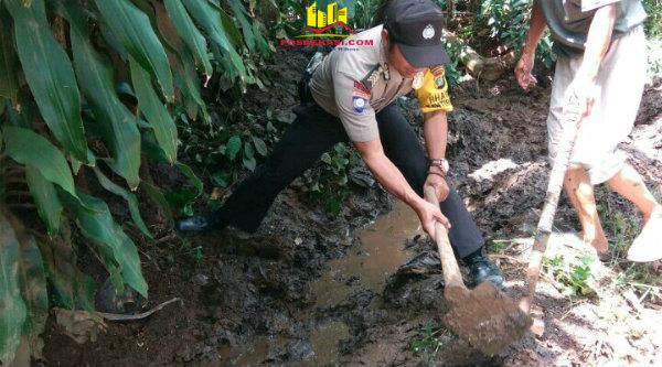 Bhabin Kamtibmas, Bripka Nursalim saat melakukan pengorekan saluran yang mampet di Kampung Sadang,[MIN]