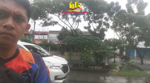 Kasi Humas Polsek Muara Gembong, Brigadir Wahyu Purwanto, dengan latar belakang genangan air di Perumahan Narogong, Kota Bekasi.[IST]