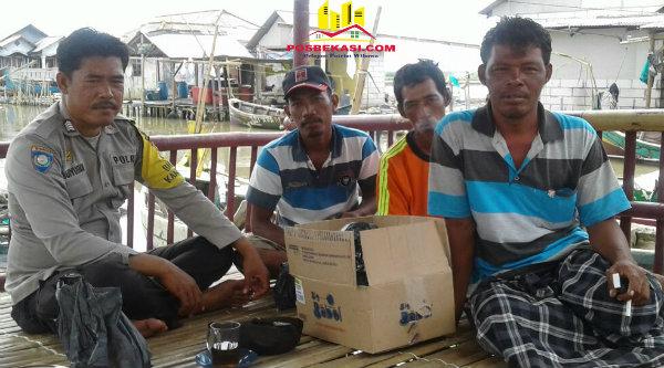 Binmaspol Desa Pantai Bahagia, Bripka Wahyudin, bersama warga kampung nelayan Muara Mati.[OJI]