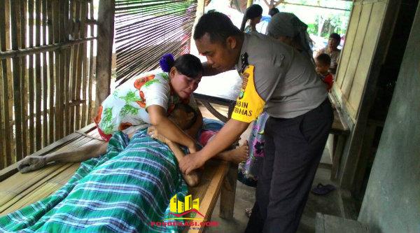 Bhabin Kamtibmas Desa Burangkeng Aipda Hari Cahyono saat membantu mengangkat jenazah korban meninggal akibat serangan jantung.[MIN]