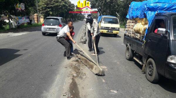 Anggota Polsek Cikbar tengah menarik balok pembatas jalan yang bergeser hingga menyempiti badan jalan Alteri Tol Cibitung.[ZEN]