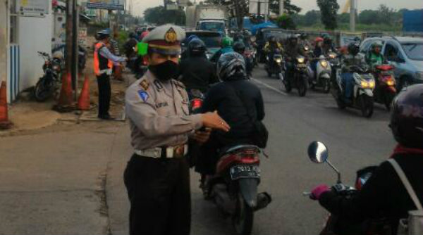 Anggota Polantas Polsek Tambun tengah mengatur lalulintas ditengah kemacetan pada petang hari.[RIS]
